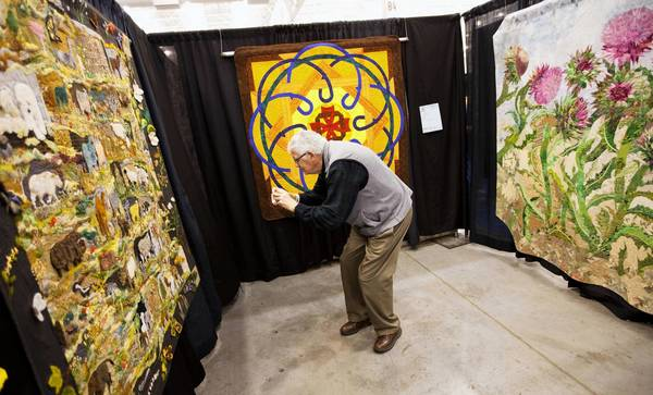 In this file photo, Hal Horan of Charlottesville takes a picture of a quilt for his daughter during Mid-Atlantic Quilt Festival at Hampton Roads Convention Center in Hampton on Friday, February 25, 2011.