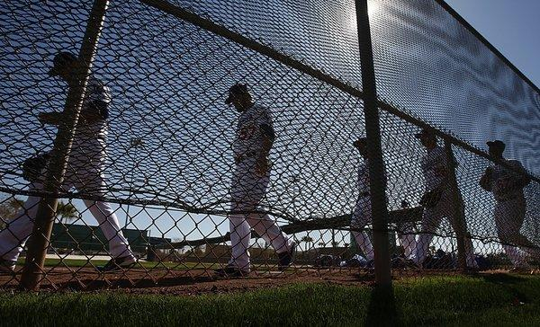 When the Dodgers go from spring training workouts to exhibition games, only a handful will be seen on television. Above, Dodgers players take to the practice field Sunday at Camelback Ranch in Phoenix.