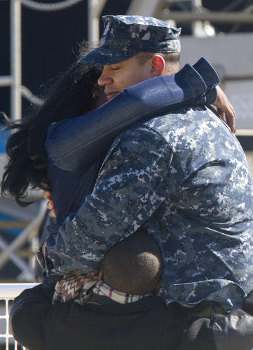 Lt. Joseph Owmby hugs his wife, Aisha Owmby, and six-year-old son, Jalen Owmby, before deploying on the USS Dwight D. Eisenhower from Naval Station Norfolk on Thursday.