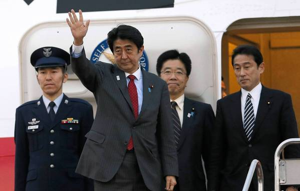 Japanese Prime Minister Shinzo Abe waves in Tokyo as he prepares to board a flight to Washington. He and President Obama will hold talks Friday.