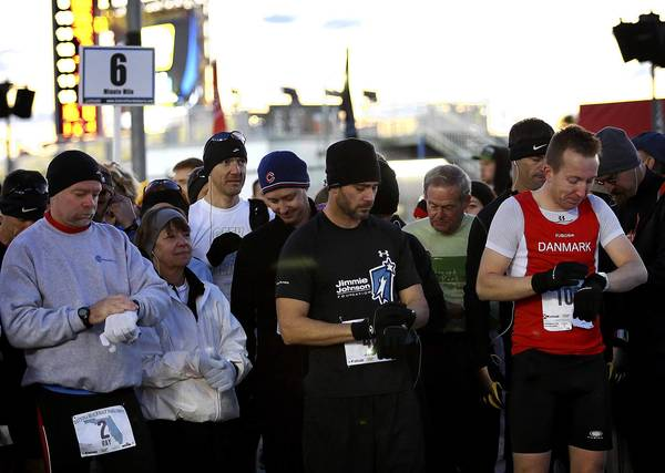 NASCAR driver Jimmie Johnson, second from right, sets his watch with other runners at the starting line of the The 5th Daytona Beach Half Marathon at Daytona International Speedway on Sunday morning, February 17, 2013. The 13.1 mile course started and ended at the speedway. The runners also ran over the International Speedway Bridgeover the Halifax River and made their way to the beach before heading back West to the track. Johnson finished 25th overall in the half marathon with a time of 1:29:49.(Jacob Langston/Orlando Sentinel)