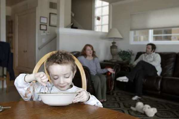 Dashiell Codd, 5, of Iowa, enjoys a bowl of cereal at a beach house in Newport Beach on Thursday.