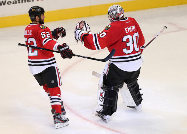 Blackhawks goalie Ray Emery celebrates with teammate Brandon Bollig (52) after beating the Vancouver Canucks on Feb. 19.