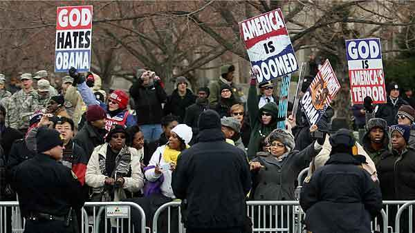 Demonstrators from the Westboro Baptist Church hold up signs along the inaugural parade route as U.S. President Barack Obama's motorcade travels from the White House to the U.S. Capitol along Pennsylvania Avenue January 21, 2013 in Washington, DC.