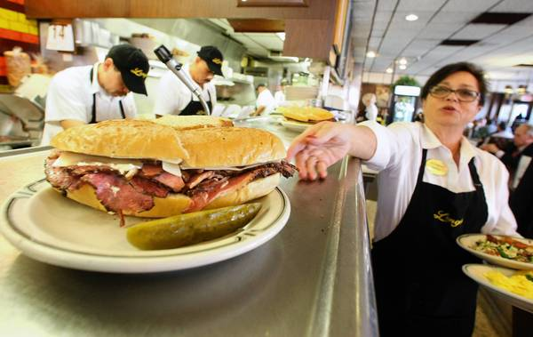 Sheila Abramson, a waitress at Langer's Delicatessen on Alvarado Street in Los Angeles, reaches for a plate while serving customers last month.