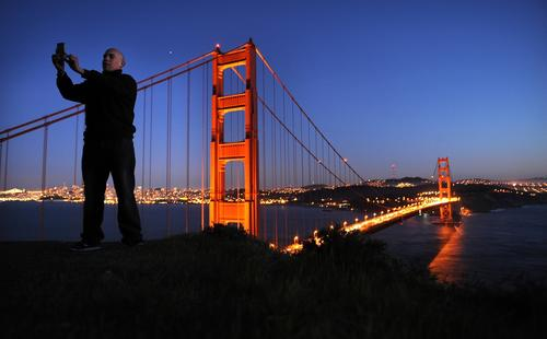 Carlos Rodriquez takes a photo of himself and the Golden Gate Bridge at dusk.