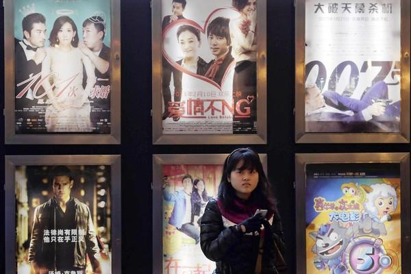 A woman stands in front of the advertisements for Chinese and foreign films at a movie theater in Shanghai.