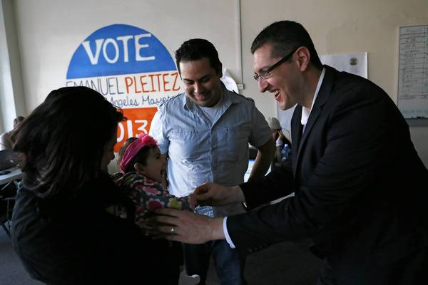 L.A. mayoral candidate Emanuel Pleitez, right, meets Naomi Reyes, the daughter of Jessica Pineda, left, and David Reyes, both of whom are volunteering at Pleitez's campaign headquarters in Boyle Heights.