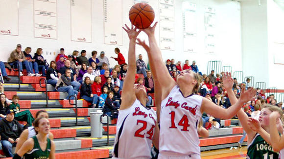 J-L's Hannah Huff (left) and Brittany Cherwinski battle for a rebound during the Lady Cards' 67-21 victory against Boyne Falls Thursday.