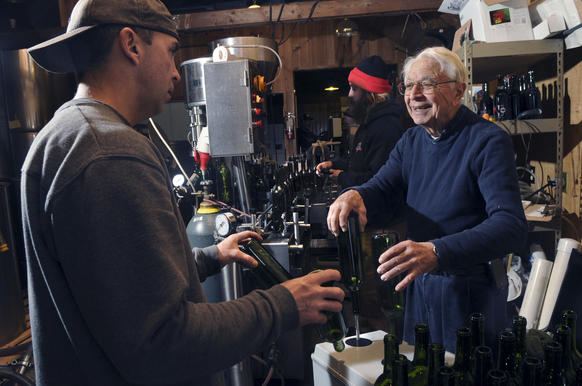 Paul DiGrazia Jr. (left) and his father, Paul DiGrazia, (right) rinse wine bottles readying them for filling with Paragran, a dessert wine, that they produce at DiGrazia Vineyards in Brookfield. Winemaker Aaron Cox corks the bottles before they are labled and packed in cases.