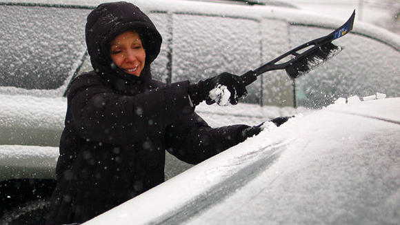 Herald Times reporter Judy Wagley cleans snow off the windshield Wednesday.