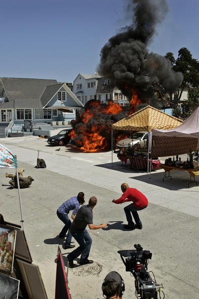 "Actors Daniela Ruah, left, Chris O'Donnell and LL Cool J react as a car is exploded on Ocean Front Walk in Venice during shooting of ""NCIS: Los Angeles"" in 2010."