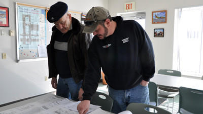 Somerset County Airport manager Dave Wright, right, and Commissioner Joe Betta go over the blueprints for several hangars that will be built later this year.