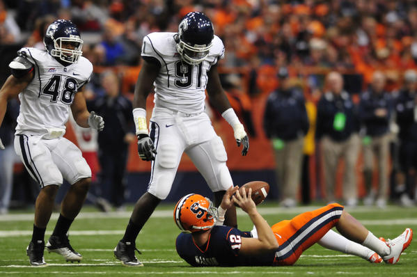 11.20.2010 - Syracuse, NY - Jesse Joseph (second from left), with teammate Trevardo Williams, stands over Ryan Nassib after sacking the Syracuse quarterback to end the second-quarter UConn leads Syracuse 10-3 after the first-half. Photograph by MARK MIRKO | mmirko@courant.com