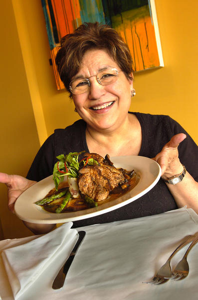 Cafe 28 owner Berta Navarro presents a dish at the restaurant, which posted on its website that it will close its doors after brunch on Sunday, Feb. 24.