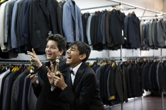 "Jawanmard Paiz, left, and Fawad Mohammadi, child stars of the film ""Buzkashi Boys,"" pose for photos holding replica Oscars. They were at Boys Suit Outlet in Hollywood getting fitted for tuxedos."
