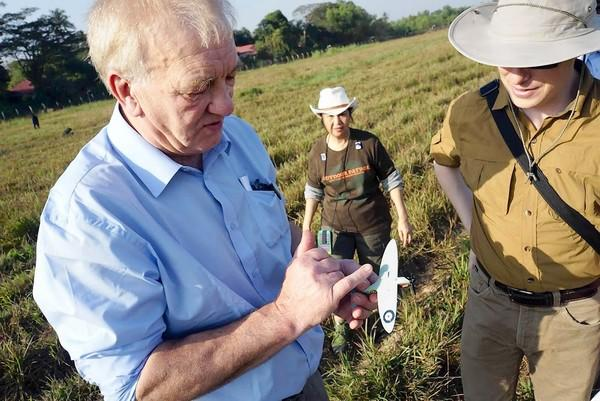 David Cundall, left, shows a model of a Spitfire plane to Tracy Spaight of Belarusian video game company Wargaming.net near the Yangon airport in Myanmar. The firm has since pulled its sponsorship of the effort to find a trove of actual vintage Spitfires that Cundall believes is buried nearby.