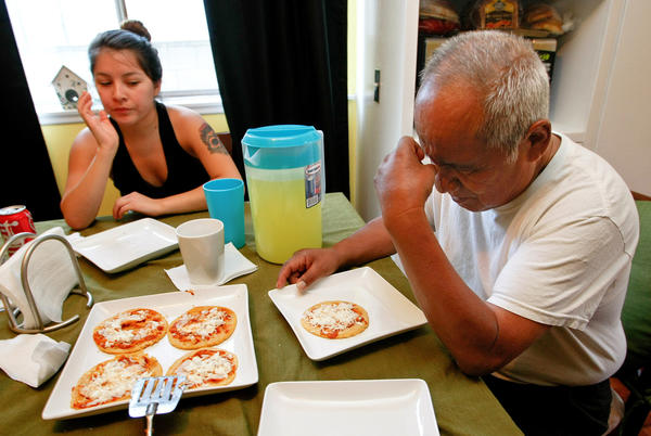 Asael Gonzalez prays before a meal with his granddaughter Erika Jovel at his son's home in Northridge.  Gonzalez, a Zapotec Indian, was a supervisor at Hamburger Hamlet for many years, recruiting hundreds from his mountain region of Oaxaca, Mexico, to work in the then-expanding chain. Many went on to become highly skilled chefs. Gonzalez now lives in Tecate, Mexico.