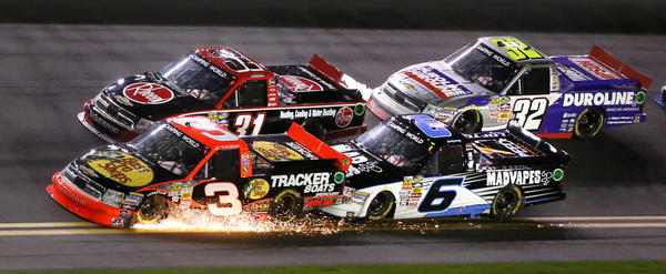 Leader #3 Ty Dillon gets pushed by Justin Lofton (#6) in a shower of sparks during the 14th Annual NextEra Energy Resources 250 truck race at Daytona International Speedway, Friday night