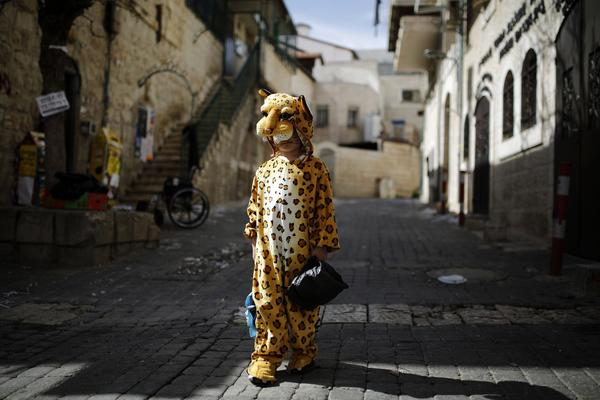 An ultra-orthodox Jewish boy wears a costume ahead of the Jewish holiday of Purim in Jerusalem's Mea Shearim neighbourhood February 22, 2013. Purim, which will be marked next week, is a celebration of the Jews' salvation from genocide in ancient Persia, as recounted in the Book of Esther.