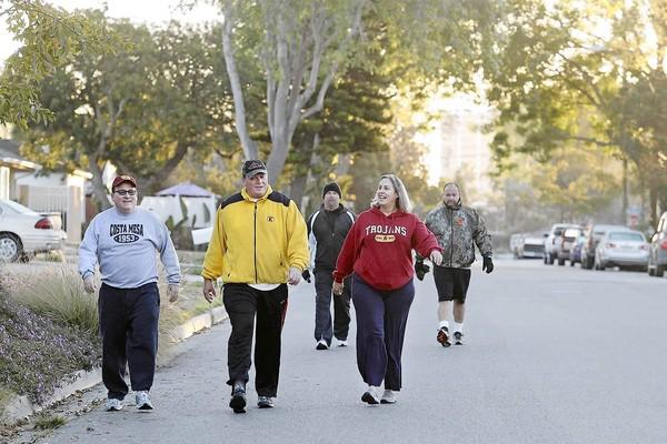 Costa Mesa Mayor Jim Righeimer, Mayor Pro Tem Steve Mensinger, former city employee Tim Sweet, resident Kristen Kirk and Estancia High football coach Mike Bargas, from left to right, make their way through Arbor Street toward to Canyon Park during an early morning walk Friday.