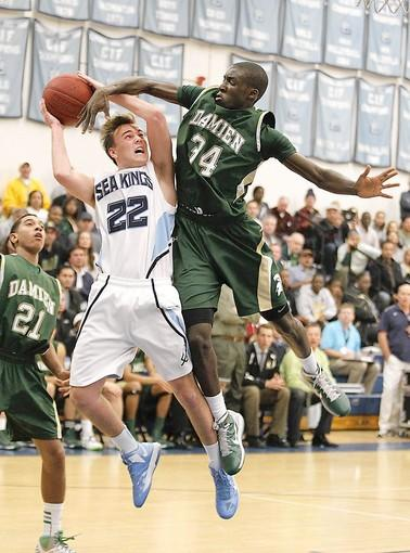 Corona del Mar High's Blake Flamson goes strong to the basket and draws the foul from Damien's Ayo Adedeji.