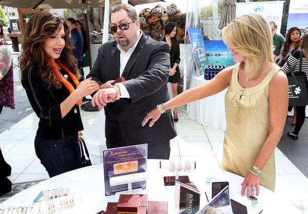 "Actress Maria Canals Barrera, left, of ""Wizards of Waverly Place""  examines Ronaldo jewelry displayed by Mike Scheser  and Lynete Wimberly at the Secret Room Events lounge presentation at the Oscars."