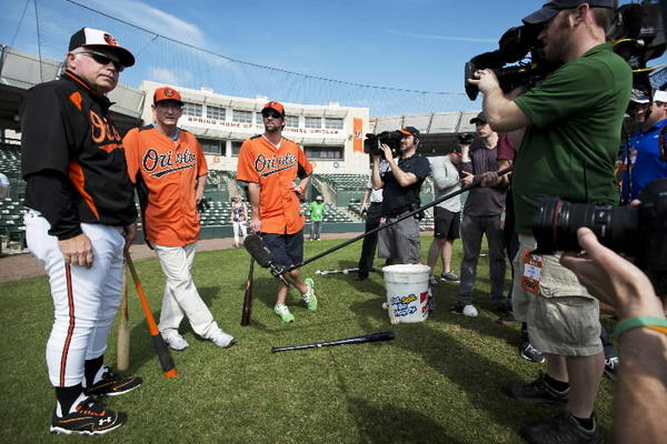 Michael Phelps poses at Orioles training camp with manager Buck Showalter and golf coach Hank Haney as Golf Channel cameras look on.