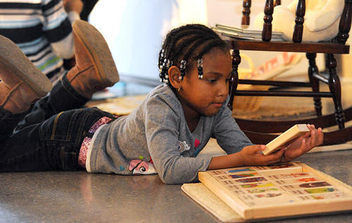 Lilianna Bryan 5, of Easton, reads a wooden story book during the Playtimes Past, an Exhibit of toys and games from the Collections of the Northampton County Historical and Genealogical Society held at the Sigal Museum Saturday morning.
