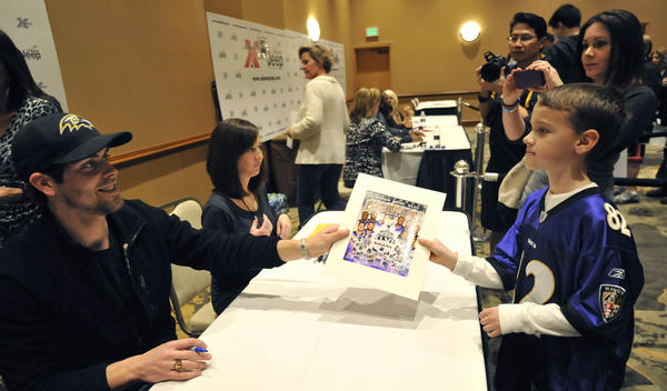 Justin Tucker, Ravens kicker, hands Dylan Musgrove, 9, Pasadena, an autograph as Dylan's mother, Kelly Musgrove, documents the moment. Tucker and other Ravens sign autographs at the Doubletree by Hilton.