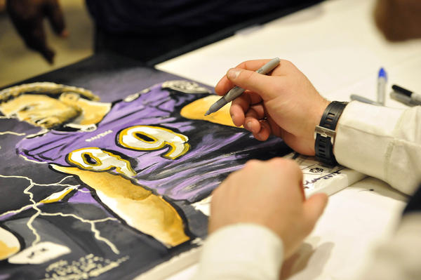 Paul Kruger looks over a painting of him before signing it. Kevin Charles, Atlanta, is the artist. Kruger is one of the Ravens players signing autographs at the Doubletree by Hilton.