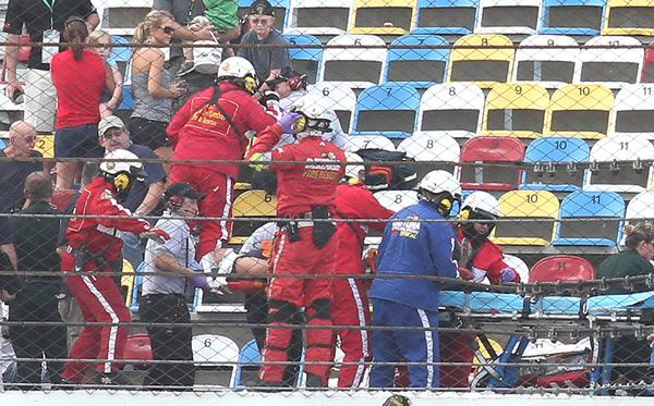 Rescue workers tend to injured fans, carrying one on a stretcher (bottom) in the grandstands following a spectacular crash involving the car of Kyle Larson on the last lap of the DRIVE4COPD 300 Nationwide Series race at Daytona International Speedway