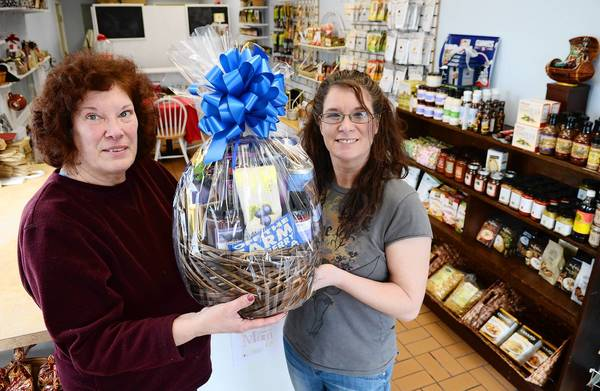 Suzanne Hinkel (left) and daughter Laura Hendricks, both of Nazareth, hold their gourmet gift basket inside of their store, Mountain Laurel Gift Baskets in Bath.