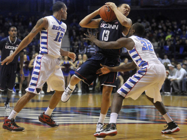 UConn's Shabazz Napier is defended by DePaul's Charles McKinney, right, and Cleveland Melvin, left, at the Allstate Arena Saturday night.