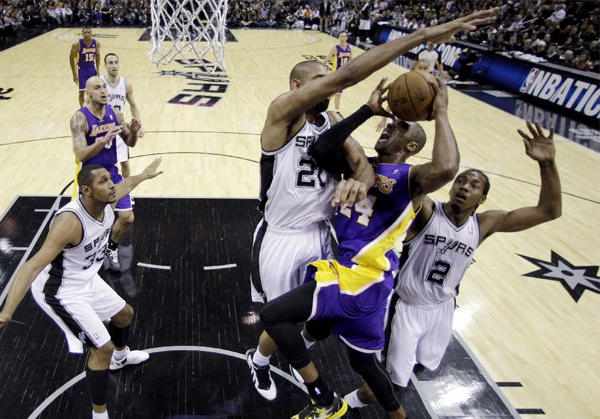 Spurs big man Tim Duncan blocks Lakers guard Kobe Bryant in front of the rim.