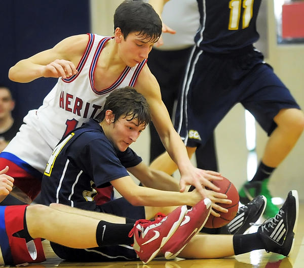 Shalom Christian's Quentin Clapper, seated, tries to keep the ball away from Heritage Academy's Nathan Patey during Saturday's MDCC Tournament boys final at Grace Academy.