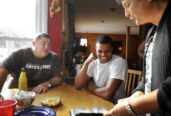 B.J. Bailey (center), a Lehigh University basketball player, looks through a photo album with Gary and Louise Baca, who invited him to move into their Absecon, N.J., home after B.J.'s mother died when he was in high school.