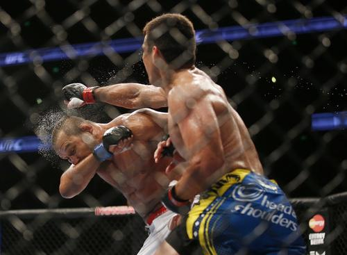 Lyoto Machida lands a punch against Dan Henderson during their light-heavyweight fight at UFC 157 on Saturday night at the Honda Center in Anaheim.