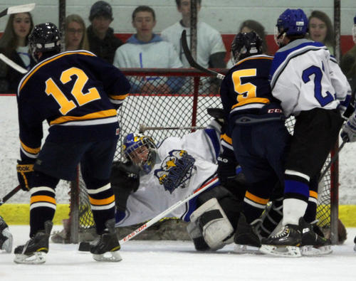 East Catholic goalie Thomas Usseglio can't keep Simsbury's Mike Gellman's shot out of the net during the first period. Simsbury won 6-2 at Champions Skating Center in Cromwell.