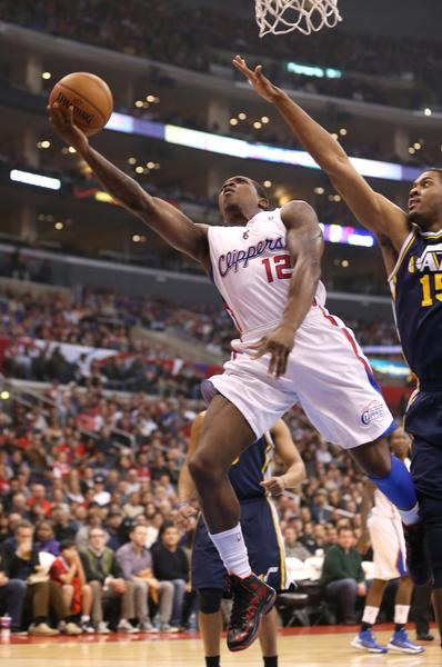 Clippers guard Eric Bledsoe lays in the ball in front of Utah forward Derrick Favors.