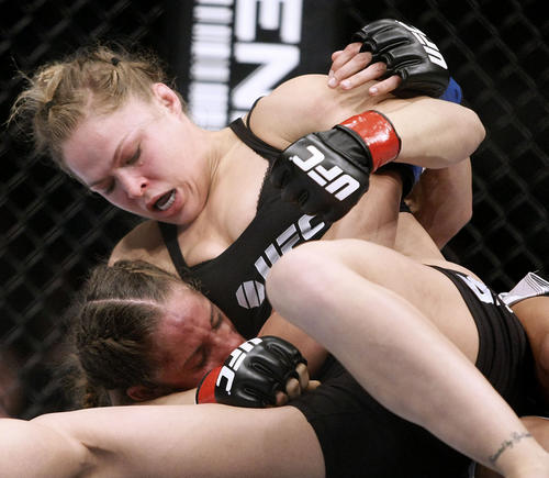 Ronda Rousey, top, punishes ex-Marine Liz Carmouche in the first round of the UFC157 to win by a tap out at the Honda Center in Anaheim on Saturday, February 23, 2013. Ronda Rousey, who trains at the Glendale Fighting Club in Glendale, defended her world championship title in the main event.