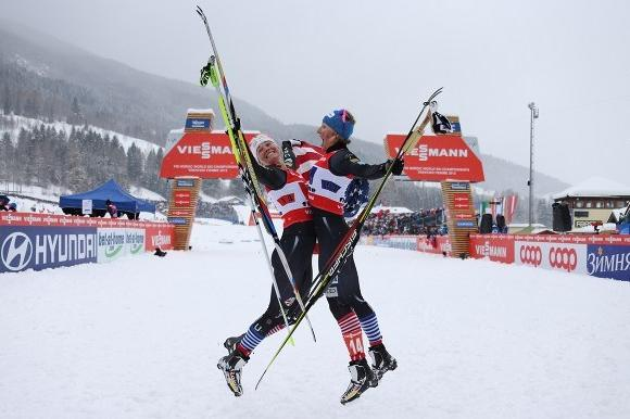 Jessie Diggins (left) and Kikkan Randall jump for joy after their historic win.  (Pierre Teyssot / AFP / Getty Images)