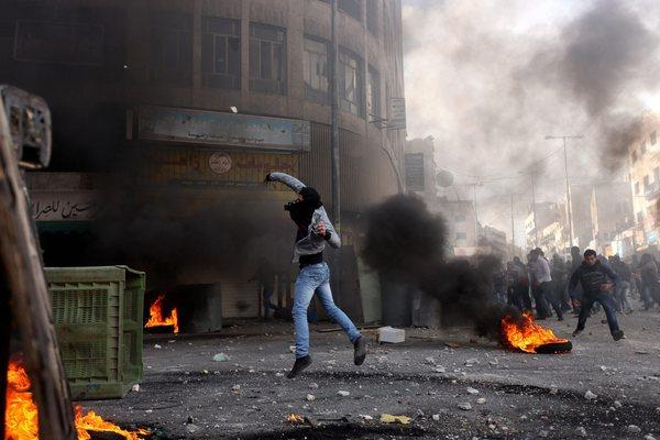 A Palestinian youth throws a stone as protesters clash with Israeli riot police in the West Bank city of Hebron.