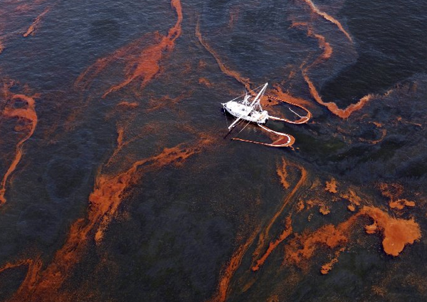 A shrimp boat helps collect oil after the 2010 spill in the Gulf of Mexico. A civil trial is set to begin this week with billions at stake for oil giant BP and Gulf states affected by the spill.