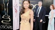"There's an interesting back story to the mustard-colored gown that ""Skyfall"" actress Naomie Harris is wearing at the 85th Academy Awards this afternoon – it's the winning design in Suzy Amis Cameron's Red Carpet Green Dress challenge and was designed by Ghana-born Michael Badger, a fashion design student at Savannah College of Art and Design, who was mentored throughout the design process by Vivienne Westwood."