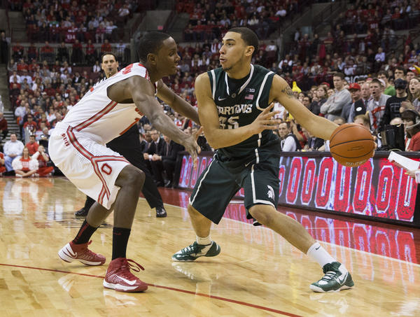 Michigan State Spartans guard Denzel Valentine (45) sends a pass around Ohio State Buckeyes forward Sam Thompson (12) at the Schottenstein Center. Ohio State won the game 68-60.
