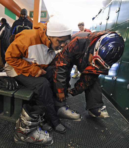 Tanya Washington, right, of the Chesapeake Ski Club, helps Tahtiana Hyman, 16, of Glen Burnie, put on her ski boots.