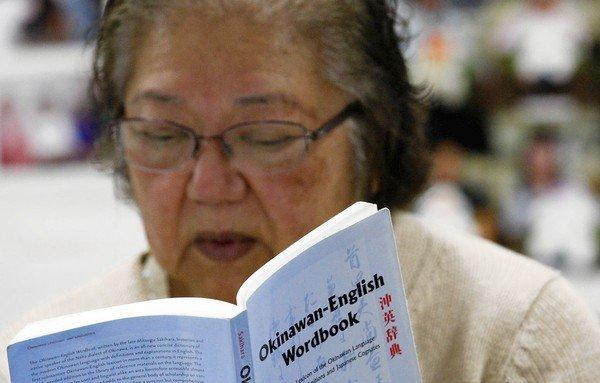 Student Dina Yogi refers to an Okinawan-English dictionary during a class in the Uchinaaguchi language in Gardena. Yogi is of Okinawan descent and is rediscovering her roots through her ancestral language. Many of the students remember their parents or grandparents using the language.