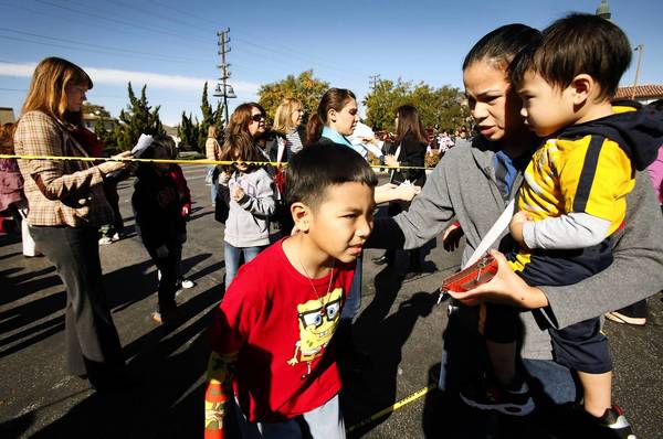 During the Jan. 7 evacuation of R.D. White Elementary in Glendale, third-grader Tobe Gragasin, 8, is released to his mother, Myra Gragasin. The bomb threat was among the reasons the school board has decided to increase security throughout the district.
