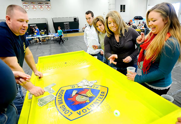 Jenny Scriever, second from right, rolls a golf ball in the Pill Game Sunday afternoon during the Hagerstown Rotary Club's annual Bull & Oyster Roast at HCC's ARCC. John Latimer, left, runs the game. Watching are Wes Stine, Tina Smartt, and Kayla Hill.